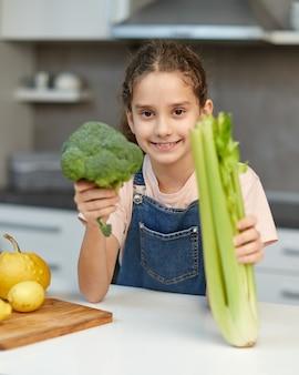 Lächelndes kleines mädchen steht in der nähe des tisches in der küche und hält grünen brokkoli und sellerie in den händen.