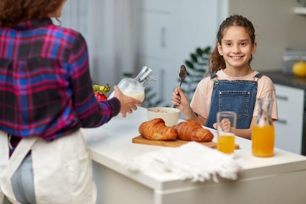 Lächelndes kleines mädchen zeigt die daumen beim gesunden frühstück zusammen mit der mutter in der küche.