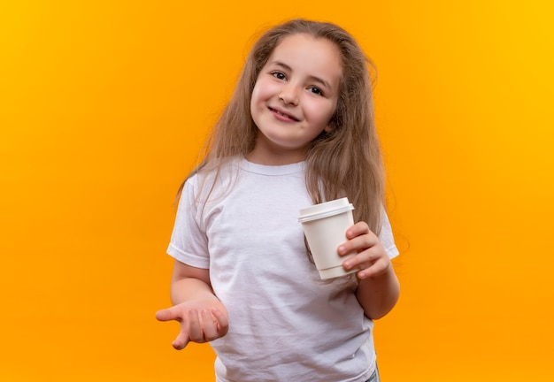 Lächelndes kleines schulmädchen, das weißes t-shirt hält, das tasse kaffee auf lokalisiertem orange hintergrund hält