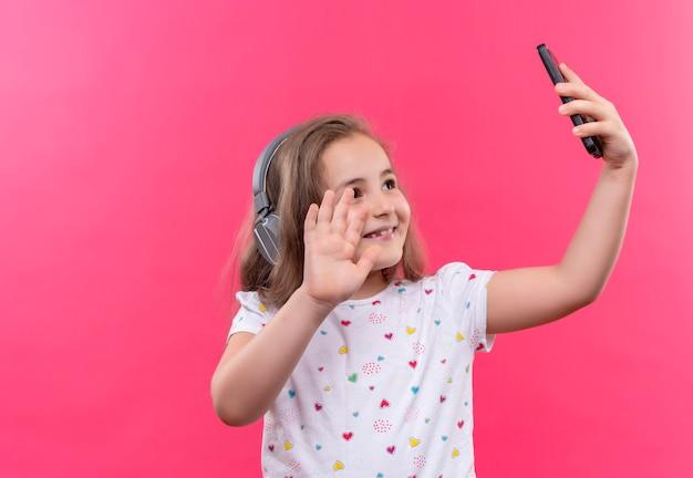 Lächelndes kleines schulmädchen, das weißes t-shirt im kopfhörer trägt, spricht am telefon auf lokalisiertem rosa hintergrund