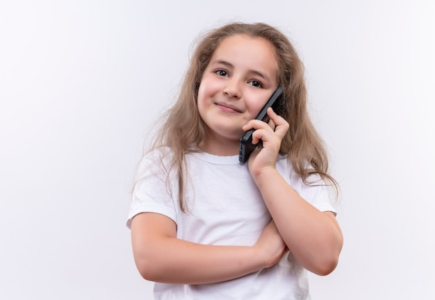 Lächelndes kleines schulmädchen, das weißes t-shirt trägt, spricht am telefon auf lokalem weißem hintergrund