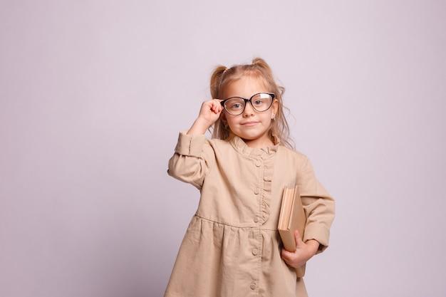 Lächelndes kleines schulmädchenmädchen in den gläsern mit einem buch auf einem grauen hintergrund. platz für text, banner