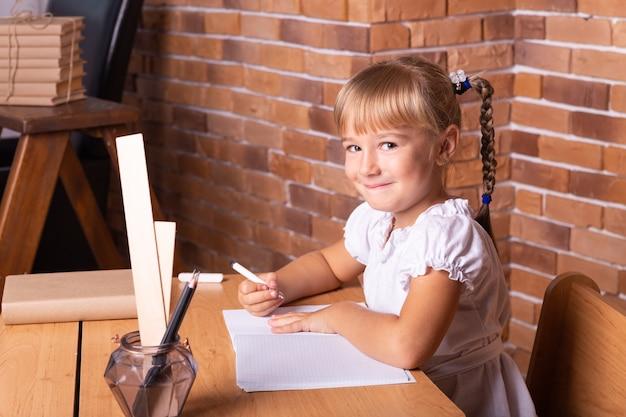 Lächelndes kleines studentenmädchen, das an einer schulbank sitzt. das kind macht hausaufgaben. vorschulbildung.