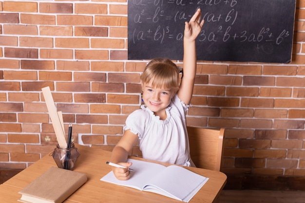 Lächelndes kleines studentenmädchen, das an einer schulbank sitzt und mathe studiert