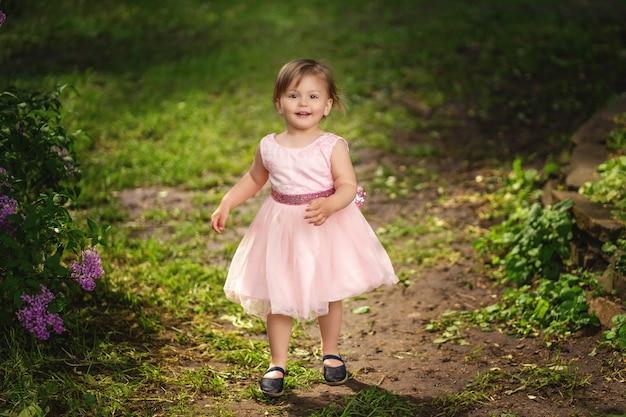 Lächelndes kleinkindmädchen laufen am frühlingspark