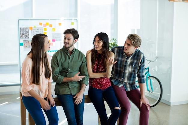 Lächelndes kreatives geschäftsteam, das im büro miteinander interagiert