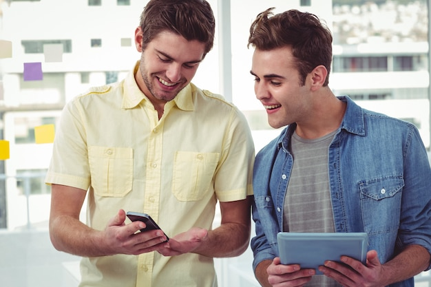 Lächelndes kreatives team, das in einer linie unter verwendung der technologie steht
