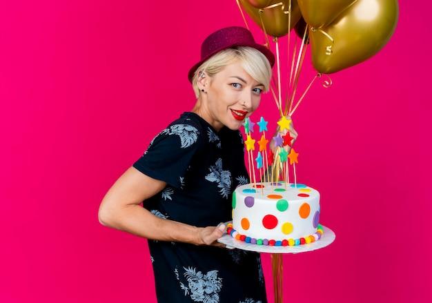 Lächelndes lächelndes junges blondes partygirl, das partyhut trägt, der in der profilansicht hält ballons und geburtstagstorte mit sternen betrachtet, die kamera lokal auf purpurrotem hintergrund mit kopienraum betrachten