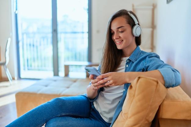 Lächelndes, lässiges, glückliches junges mädchen, das auf einem sofa sitzt und smartphone und drahtlose kopfhörer verwendet, um videoinhalte online anzusehen