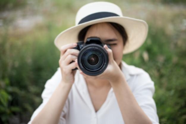Lächelndes lebensstilporträt des sommers des netten frauenwanderers, der spaß in der stadt in thailand am abend mit dem kamerareisefoto des fotografen macht bilder im hippie-arthut hat