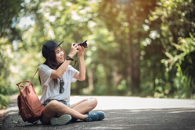 Lächelndes lebensstilporträt im freien der recht jungen frau, die spaß mit kamera hat