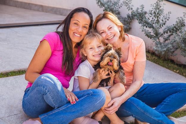 Lächelndes lesbisches paar mit kinder- und haustierwelpen. lesbisches paar hält mit ihrer adoptivtochter, adoptionskonzept.