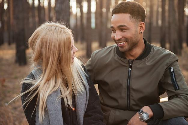 Lächelndes liebendes paar, das draußen im wald sitzt.