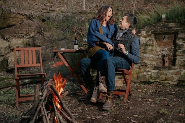 Lächelndes liebespaar, das wein im garten mit lagerfeuer isst und trinkt