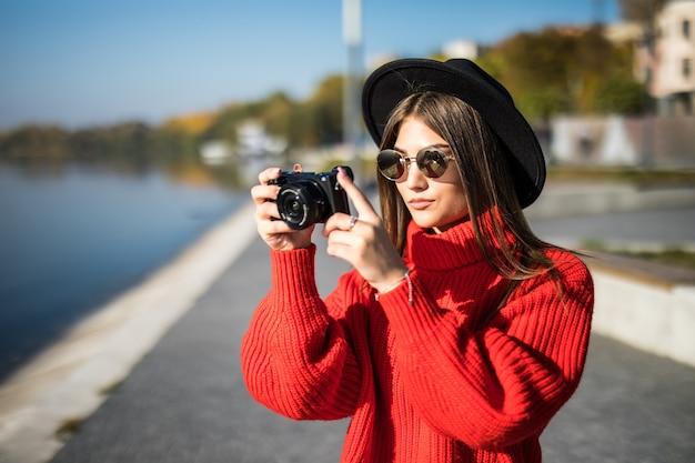 Lächelndes lifestyle-porträt im sommer im freien einer hübschen jungen frau, die sich abends in der stadt in europa mit einem kamerareisefoto des fotografen amüsiert, der bilder in brille und hut im hipster-stil macht
