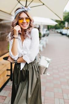 Lächelndes lockiges mädchen in den gelben gläsern, die am sommertag unter regenschirm stehen
