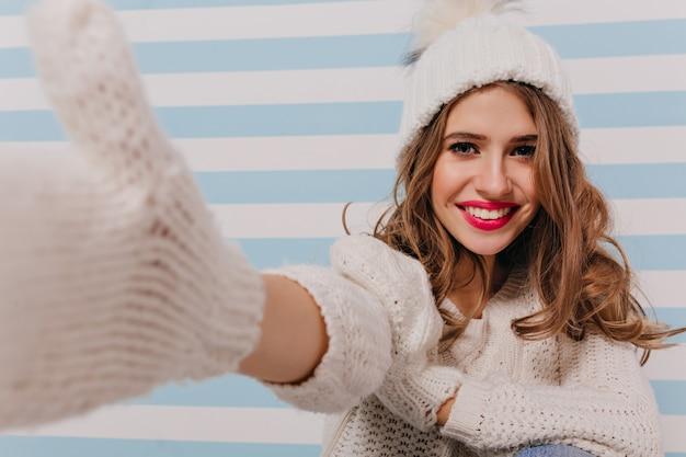 Lächelndes, lockiges slawisches model mit sanftem make-up und selfie. porträt des mädchens in gestrickter kleidung auf gestreifter blauer wand