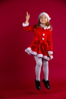 Lächelndes lustiges schulmädchen im roten weihnachtskostüm mit der roten weihnachtsmannmütze, die auf rote wand mit viel platz springt. kid zeigt mit dem finger. .