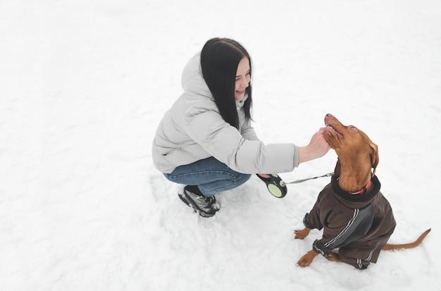 Lächelndes mädchen auf der straße mit einem schönen hund, der kleidung trägt, die geht.