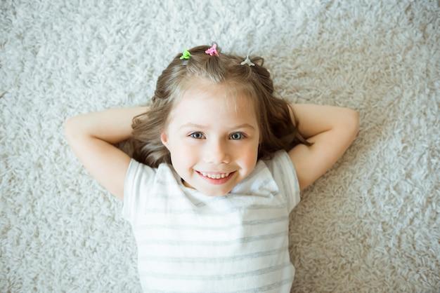 Lächelndes mädchen auf einem weißen teppich.