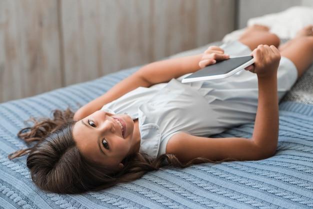 Lächelndes mädchen, das auf dem bett in der hand hält digitale tablette liegt