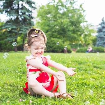 Lächelndes mädchen, das auf dem grünen gras spielt mit transparenten blasen sitzt