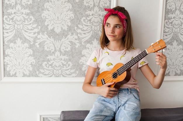 Lächelndes mädchen, das auf dem sofa justiert ukulele und das denken sitzt