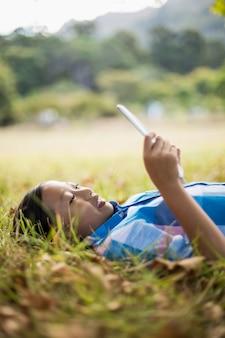 Lächelndes mädchen, das auf gras liegt und digitale tablette verwendet