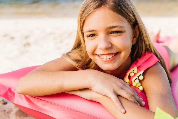 Lächelndes mädchen, das auf luftmatratze auf strand stillsteht