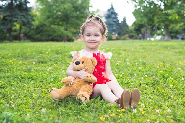 Lächelndes mädchen, das den teddybären sitzt auf dem grünen gras hält