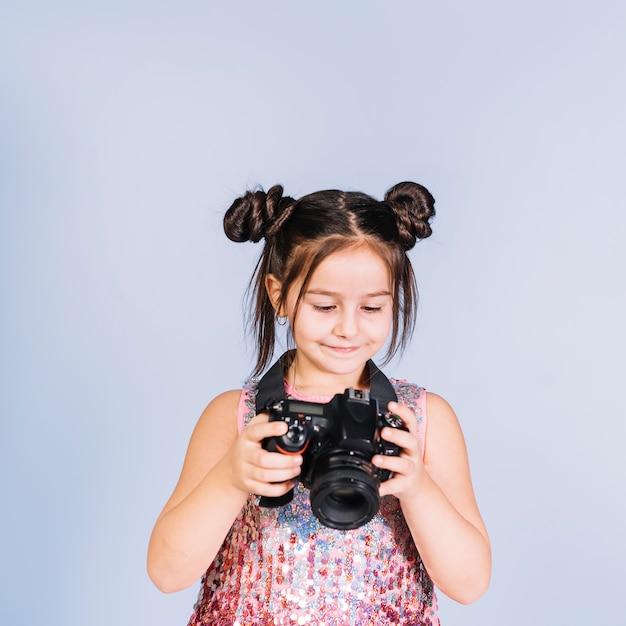 Lächelndes mädchen, das digitalkamera gegen blauen hintergrund betrachtet