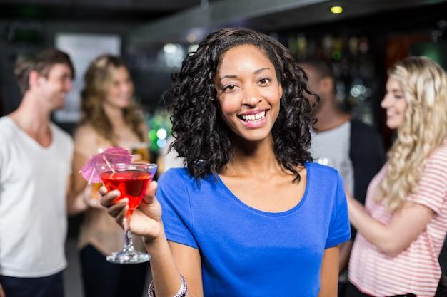 Lächelndes mädchen, das ein cocktail mit ihren freunden hat