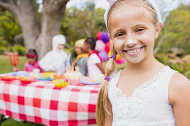 Lächelndes mädchen, das ein kostüm während einer geburtstagsfeier trägt
