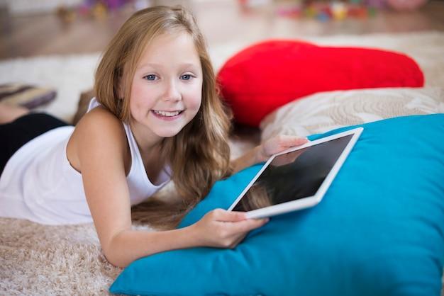 Lächelndes mädchen, das eine digitale tablette hält