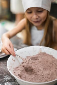 Lächelndes mädchen, das einen löffel kakaopulver von der schüssel nimmt