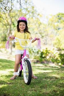 Lächelndes mädchen, das fahrrad fährt