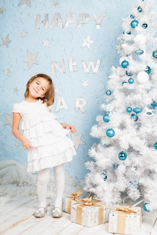 Lächelndes mädchen, das fast weihnachtsbaum mit weihnachtsdekorationen und -geschenken tanzt