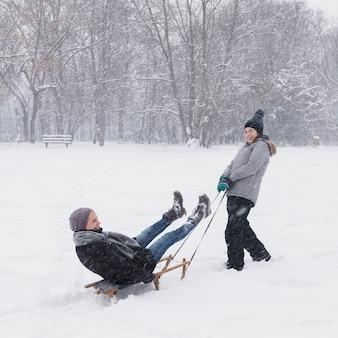 Lächelndes mädchen, das ihre mutter auf schlitten am wald während des schnees zieht