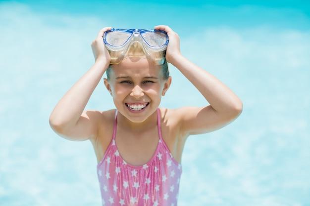 Lächelndes mädchen, das ihre schwimmbrille nahe schwimmbad hält
