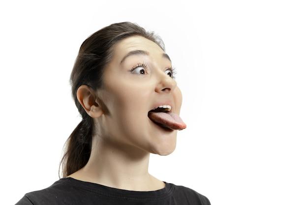Lächelndes mädchen, das ihren mund öffnet und die lange große riesige zunge isoliert auf weißer wand zeigt. sieht schockiert, angezogen, verwundert und erstaunt aus. exemplar für anzeige. menschliche emotionen, marketing.
