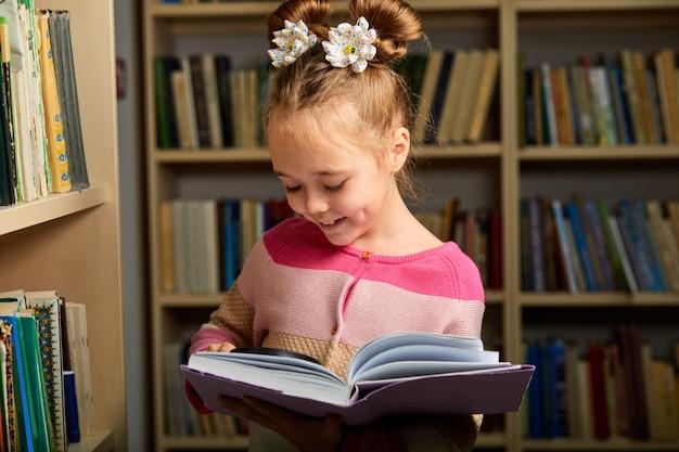 Lächelndes mädchen, das lupe benutzt, um bücher besser zu lesen, sie genießt zeit der ausbildung, des lernens. in der bücherei