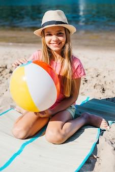 Lächelndes mädchen, das mit ball auf strand sitzt