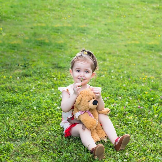 Lächelndes mädchen, das mit riechender blume des teddybären im park sitzt