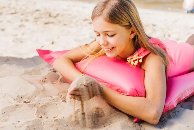 Lächelndes mädchen, das mit sand auf luftmatratze auf strand spielt