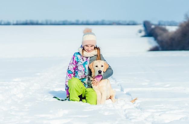 Lächelndes mädchen, das reizenden hund auf schneebedecktem feld kuschelt