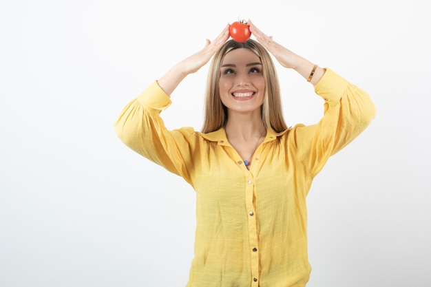 Lächelndes mädchen, das rote tomate auf ihrem kopf auf weißer wand hält.