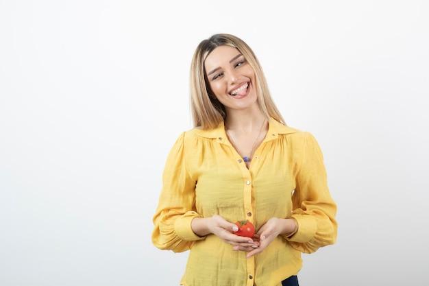 Lächelndes mädchen, das rote tomate hält und ihre zunge auf weiß herausstreckt.