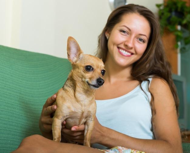Lächelndes mädchen, das russkiy toy terrier hält