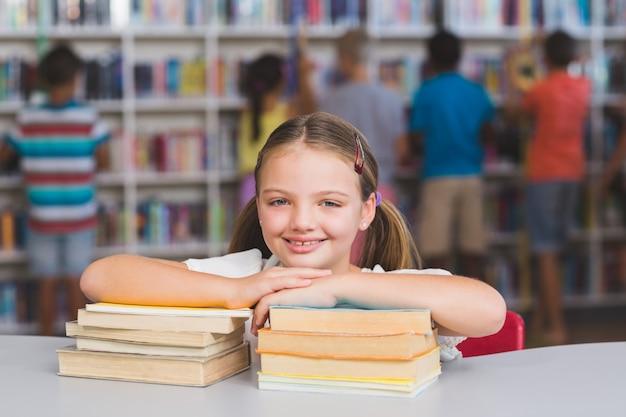 Lächelndes mädchen, das sich auf stapel bücher in bibliothek stützt