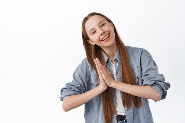 Lächelndes mädchen, das sich verbeugt und namaste zeigt, dankbare geste, dankbarkeit ausdrückt, glücklich und zufrieden über weißer wand steht